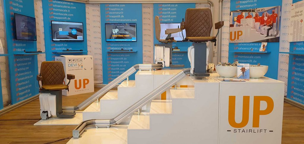 Zu sehen ist der UP-Treppenlift Showroom in den Niederlanden. Abgebildet sind zwei weiße Mustertreppen. Auf jeder Treppe ist ein UP-Treppenlift mit unterschiedlichen Schienenverläufen montiert. Auf der vorderen Treppen befindet sich ein Lift mit einem kurvigen Schienenverlauf. Ein gerader Schienenverlauf befindet sich auf der dahinter liegenden Treppe. Rubrik Treppenlift/Treppenlift kaufen/Treppenlift mieten/Kosten Treppenlift/Preise Treppenlift/Föderung Treppenlift